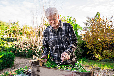 Senior man barbecueing vegetables in his garden - p300m2159841 by VITTA GALLERY