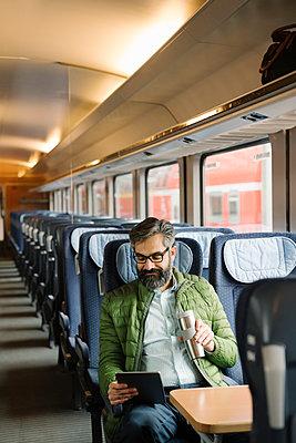 Man sitting in train using tablet - p300m2188119 by Hernandez and Sorokina