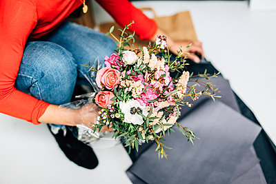 Neck down view of female florist wrapping flower bouquet in florists workshop - p429m1418092 by Alys Tomlinson