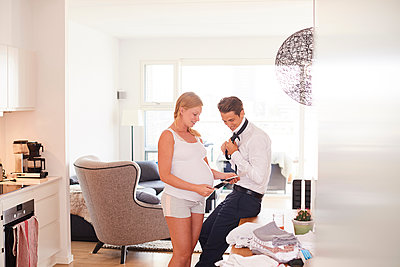 Pregnant couple looking at ultrasound pictures in living room - p429m1513752 by Jakob Helbig