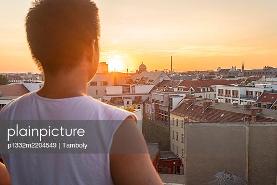 Junge Mann beobachtet den Sonnenuntergang über Berlin - p1332m2204549 von Tamboly