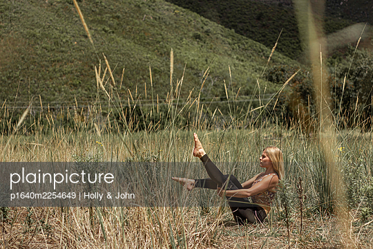 Blond woman practices gymnastics in the meadow - p1640m2254649 by Holly & John