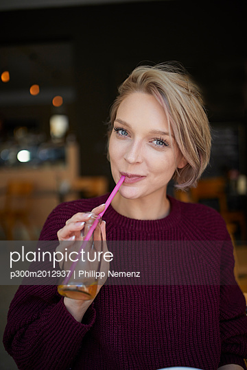 Portrait of smiling blond woman drinking with straw from bottle in a cafe - p300m2012937 von Philipp Nemenz