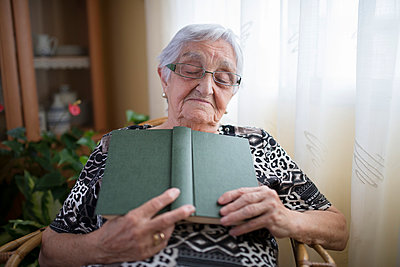 Senior woman having a nap with book in her hands at home - p300m1058958f by Ramon Espelt