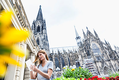 Germany, Cologne, young woman with digital tablet in front of Cologne Cathedral - p300m1188550 by Jo Kirchherr
