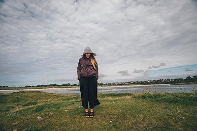 France, Brittany, Landeda, Dunes de Sainte-Marguerite, young woman standing at the coast - p300m1580841 von Gustafsson