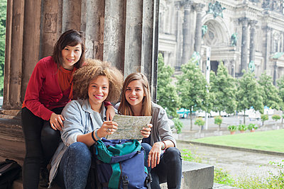 Portrait of young female tourists sitting with map at Altes Museum against Berlin Cathedral, Germany - p301m1498655 by Larry Washburn