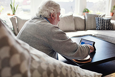 Senior man using digital tablet while sitting on sofa at home - p426m1468338 by Maskot