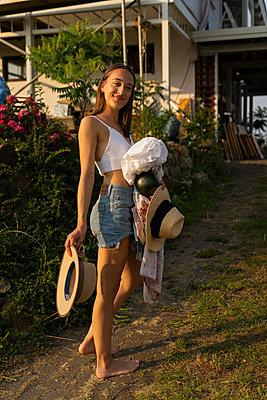 Junge Frau steht lächelnd im Garten - p432m2230914 von mia takahara