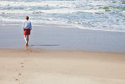 Man walking on beach - p956m1044262 by Anna Quinn