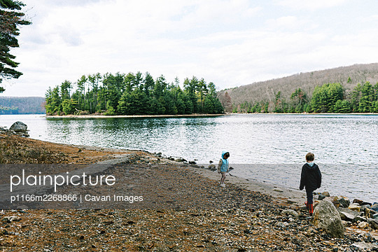 Two kids playing at the rocky beach of a lake surrounded by forest - p1166m2268866 by Cavan Images