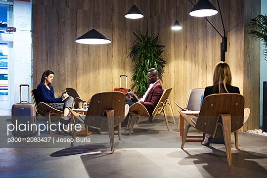 Business people sitting in hotel lobby, working