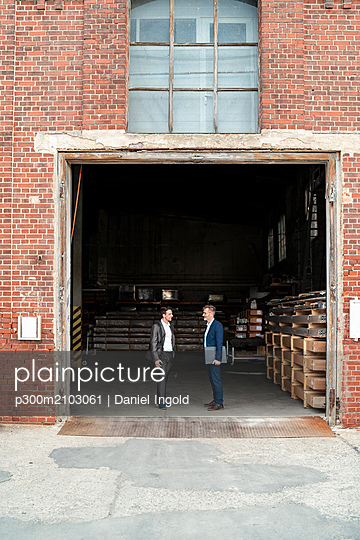 Two businessmen talking at an old storehouse - p300m2103061 by Daniel Ingold