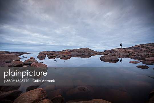 Woman standing by a rock pool in Vasterbotten, Sweden - p352m1523770 by Calle Artmark