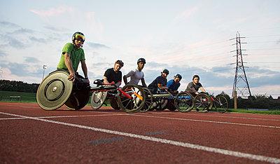 Portrait confident, determined paraplegic athletes training for wheelchair race on sports track - p1023m2067567 by Martin Barraud