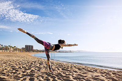 Determined woman performing yoga in Warrior 3 pose on beach - p1166m1163544 by Cavan Images
