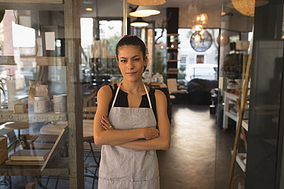 Portrait of waitress standing with arms crossed in coffee shop - p1315m1565111 by Wavebreak