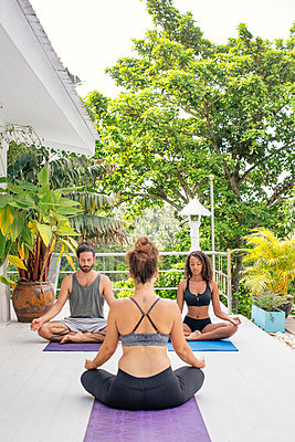 Two women and a man practicing yoga on terrace - p300m1588153 by Mosu Media