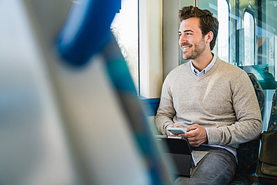 Smiling young man with smartphone and tablet on a train - p300m2155864 by Uwe Umstätter