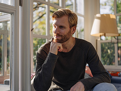 Relaxed man sitting in sunroom at home - p300m2167216 by Kniel Synnatzschke