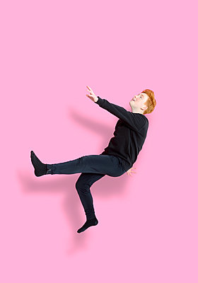 Jumping girl in front of pink background - p427m2272317 by Ralf Mohr