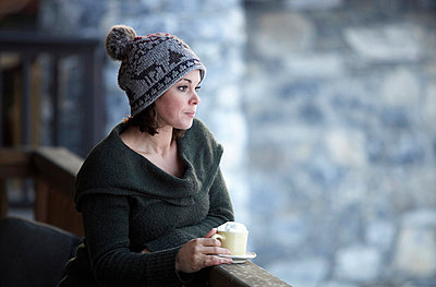Woman with hot drink on chalet balcony - p42914148f by Ross Woodhall