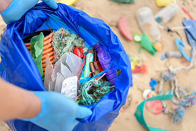 Man holding bag full of plastic pollution collected on beach, North East England, UK - p429m2004552 by Monty Rakusen