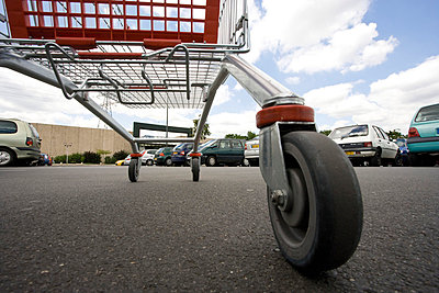 Shopping cart in parking lot, surface level view - p62314865f by James Hardy
