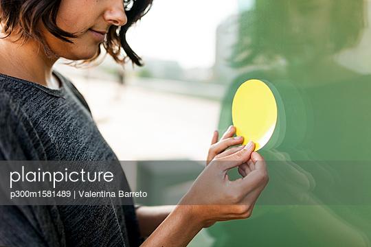 Close-up of woman attaching a sticker on a glass pane - p300m1581489 von Valentina Barreto