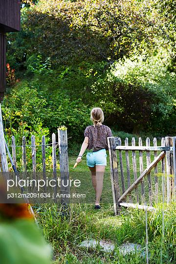 Girl in garden - p312m2091634 by Anna Kern