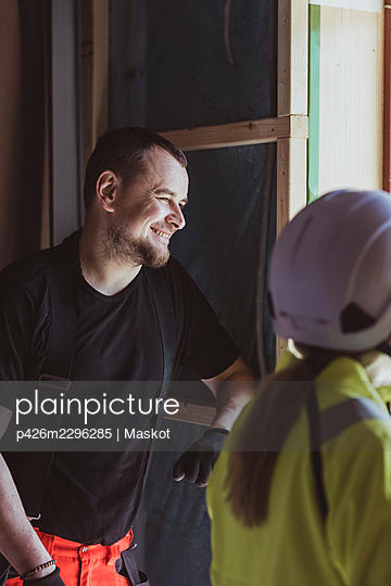 Smiling male construction worker discussing with female builder at site - p426m2296285 by Maskot
