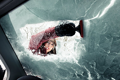 Portrait of young woman cleaning snow from car's windscreen - p300m2180730 by Wilfried Feder