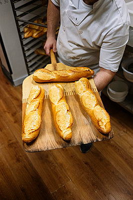 Male chef holding freshly baked baguette on pizza peel in bakery kitchen - p300m2242871 by Jose Luis CARRASCOSA