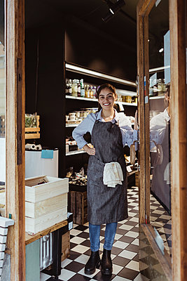 Portrait of smiling young female owner standing by door of delicatessen shop - p426m2270667 by Maskot