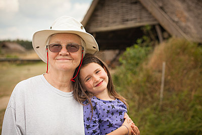Caucasian grandmother hugging granddaughter in backyard - p555m1409574 by Shestock