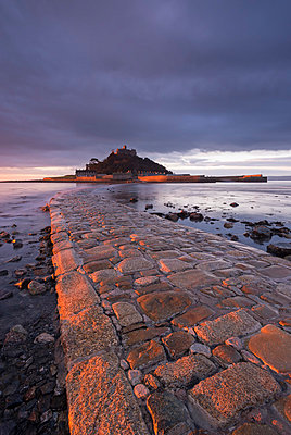 First light of day in winter on the stone causeway leading to St. Michaels Mount, Marazion, Cornwall, England, United Kingdom, Europe - p871m1017472 by Adam Burton