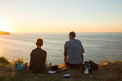 Vater und Sohn betrachten Sonnenuntergang am Meer - p948m1465593 von Sibylle Pietrek