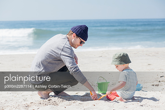 Man and son playing with sand toys by water at beach - p300m2287114 by Ashley Corbin-Teich