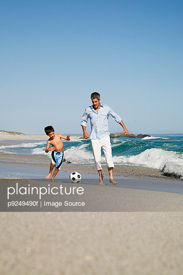 Father and son playing football by the sea - p9249490f by Image Source