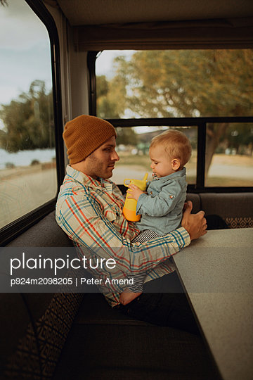 Father and baby relaxing in motorhome, Wanaka, Taranaki, New Zealand - p924m2098205 by Peter Amend