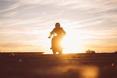 Silhouette of man riding custum motorcycle at sunset - p300m2081263 by Oscar Carrascosa Martinez