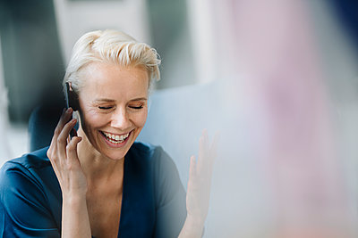 Close-up of cheerful businesswoman with eyes closed talking over smart phone in office - p300m2214169 by Kniel Synnatzschke