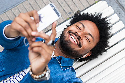 Close-up of cheerful man with afro hair listening music and using mobile phone while lying on bench - p300m2243323 by NOVELLIMAGE
