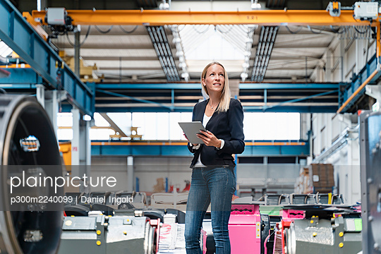 Businesswoman holding digital tablet looking away while standing in factory - p300m2240099 von Daniel Ingold
