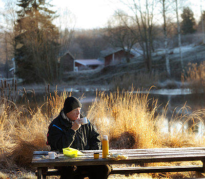 Man drinking coffee by grass and peaceful lake with blurred houses and trees in the background - p1025m788993f by Peo Quick