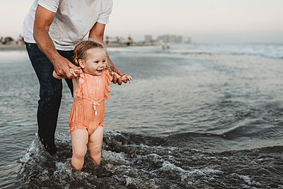 Toddler girl splashing in ocean with father at sunset - p1166m2165921 by Cavan Images