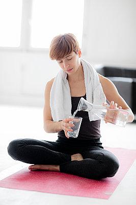 Frau nach dem Yoga - Wasser einschenken - p1212m1123407 von harry + lidy