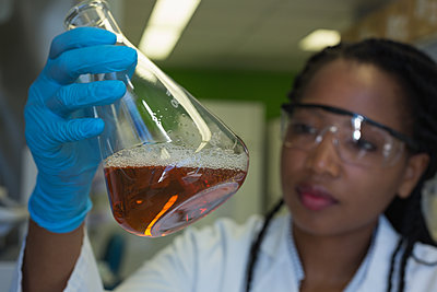 Scientist checking a solution in conical flask - p1315m1579292 by Wavebreak