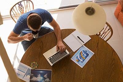 Man using laptop while having coffee - p1315m2041254 by Wavebreak