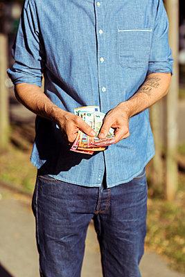 Mann hält einige Geldscheine in der Hand - p432m1586840 von mia takahara